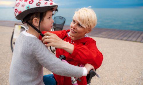 maman attache le casque de vélo sur la tête de son fils