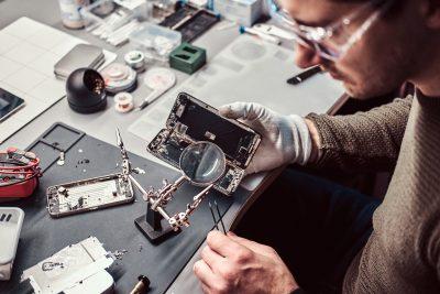 Technicien Électronique réparation smartphone endommagé dans l'atelier