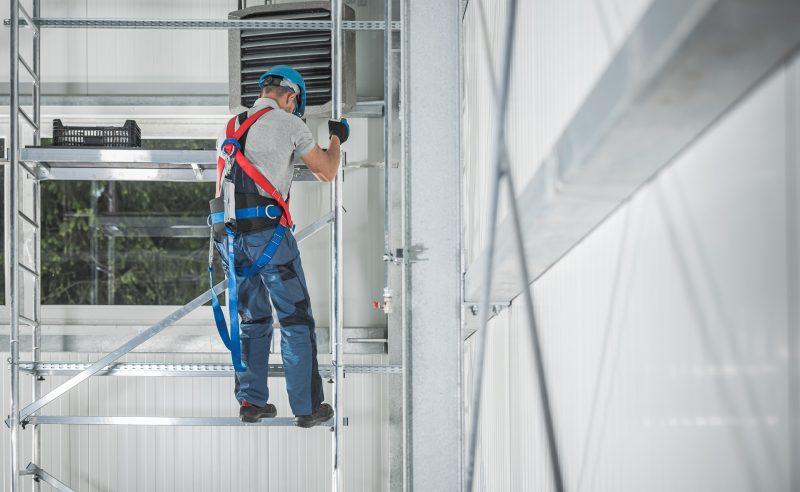 Ouvrier du bâtiment grimpant sur la structure d'échafaudage