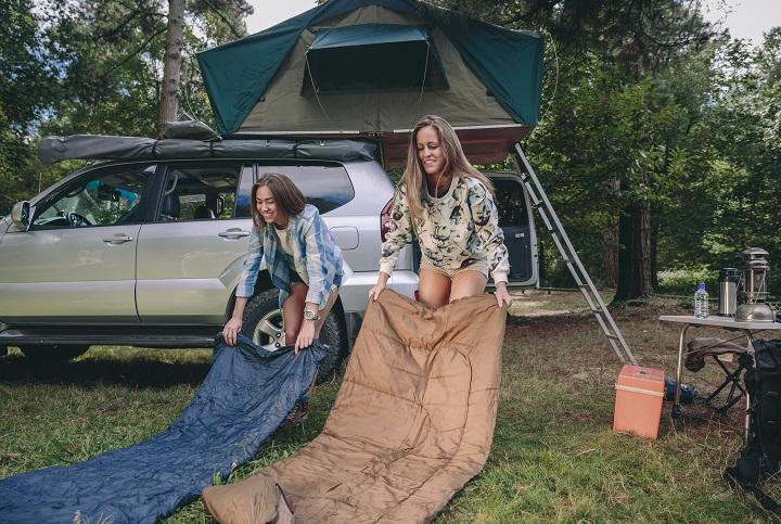 Jeunes femmes plaçant des sacs de couchage sur l'herbe